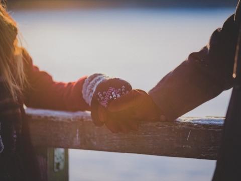 Personen halten Händchen im Winter mit Handschuhen