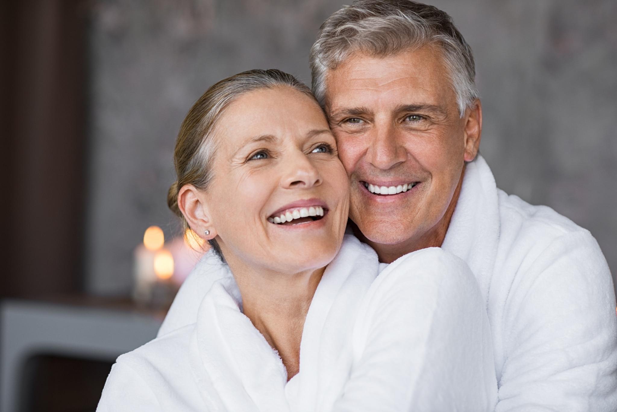 Best Ager Paar in Bademantel umarmt sich lachend