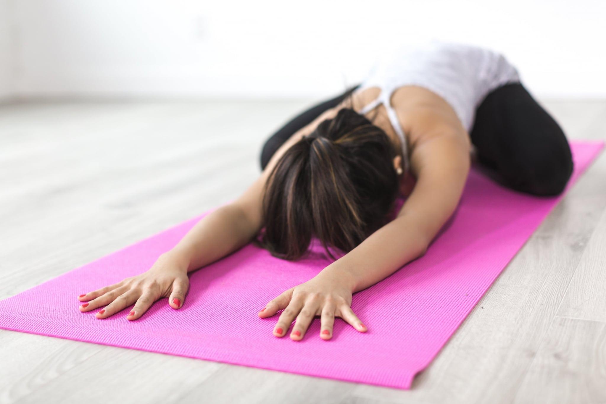 Frau in einer Yoga-Position auf einer Matte