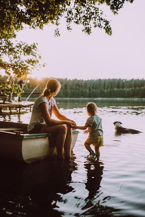 Frau mit Kleinkind und Hund am See, im Hintergrund Tannen