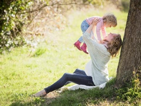 Frau lehnt an Baum und hebt Kind in die Luft