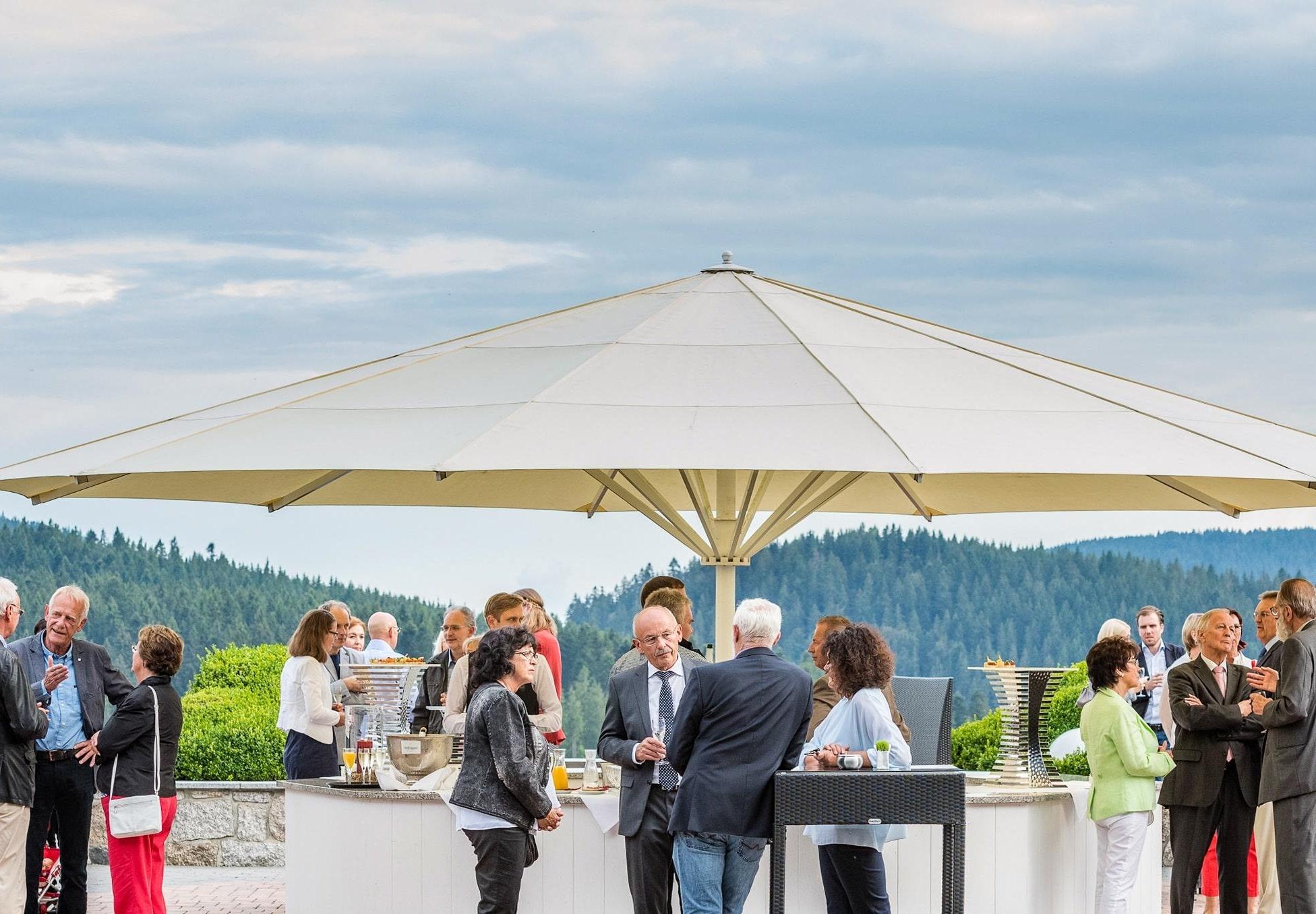 Personen bei Tagungspause auf Terrasse des Vier Jahreszeiten am Schluchsee