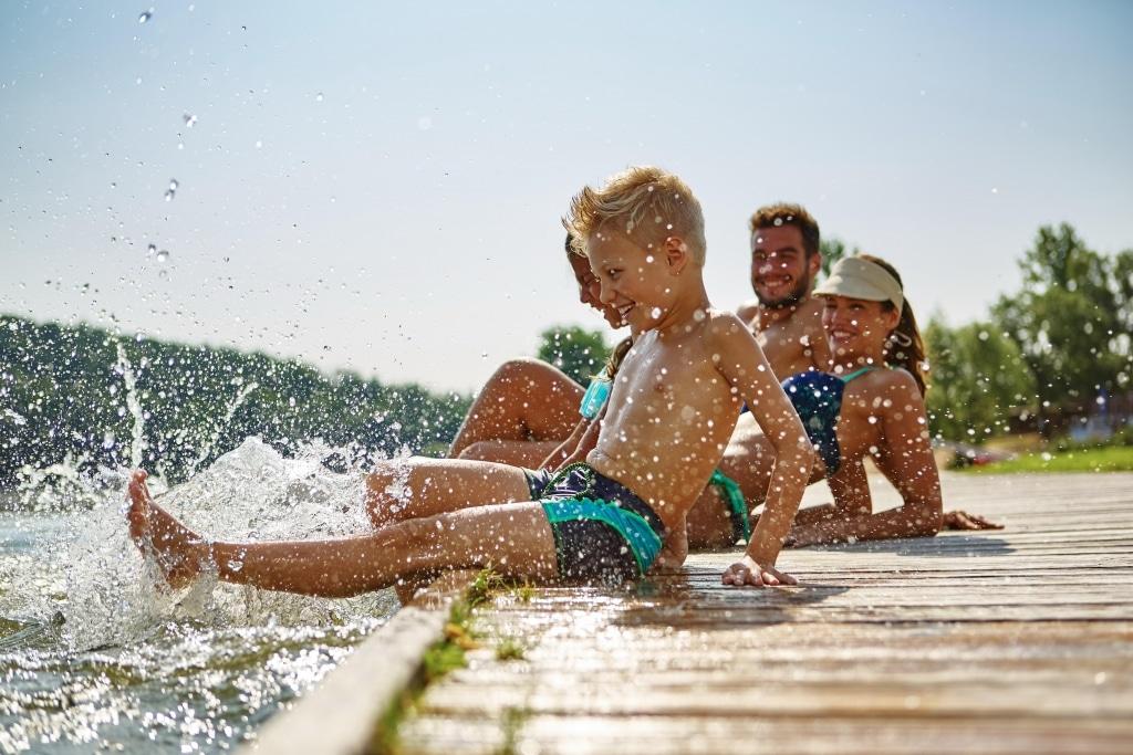 Familie mit zwei Kindern am See - Fuesse im Wasser