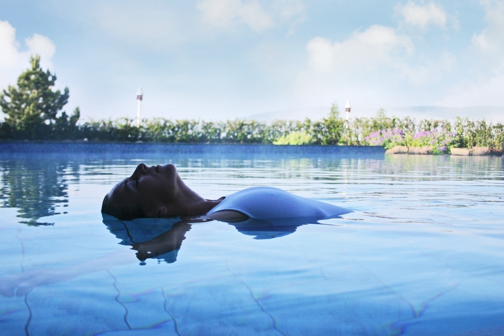 Frau schwebt auf dem Wasser im Pool im Vier Jahreszeiten am Schluchsee