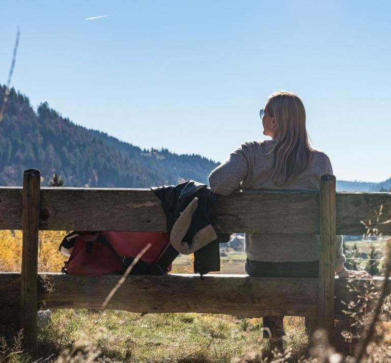 Wanderin bei einer Wanderpause auf einer Bank - © HTG