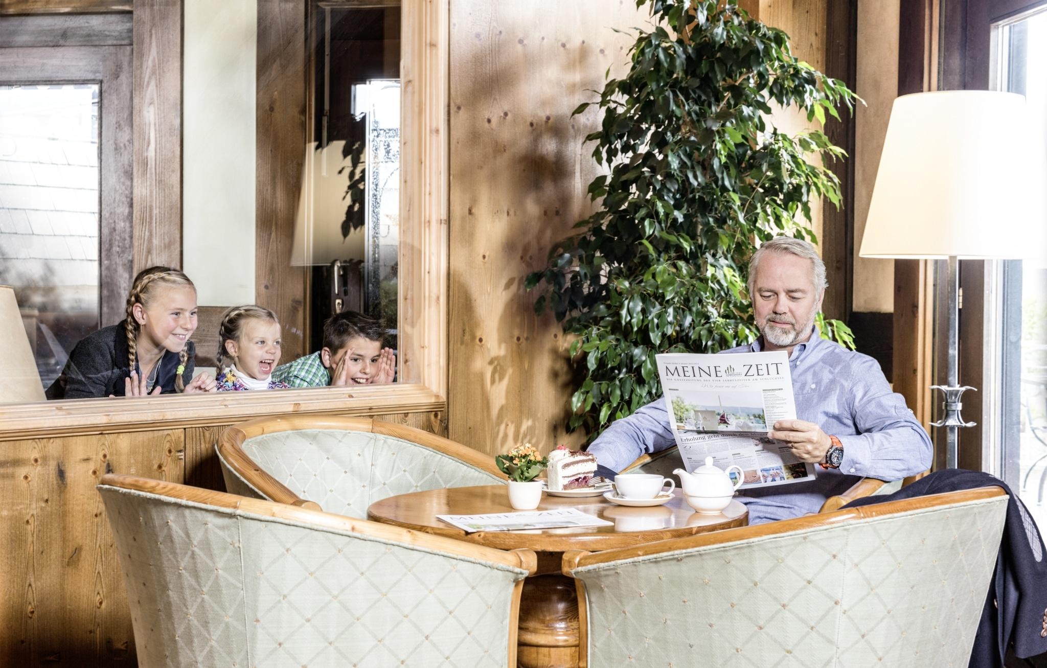 Kinder schauen Mann beim Lesen der Zeitung zu