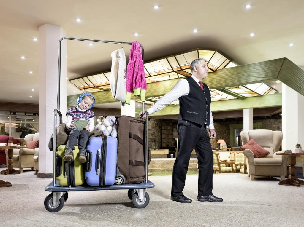 Kind sitzt auf Kofferwagen und wird von Rezeptionsmitarbeiter gezogen