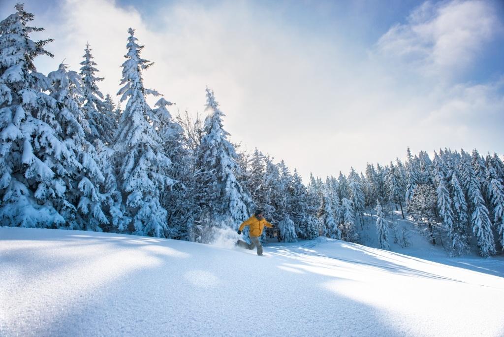 Mann rennt durch hohen Schnee, im Hintergrund verschneite Tannen