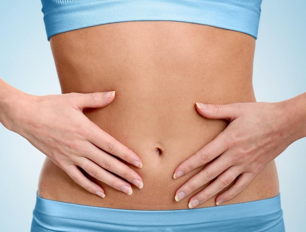 Frau legt Hände auf Ihren Bauch - Potamos Gesundheitskur
