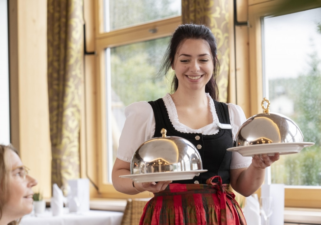 Kellnerin bringt Dinner unter Wärmeglocken im Restaurant Kachelofen