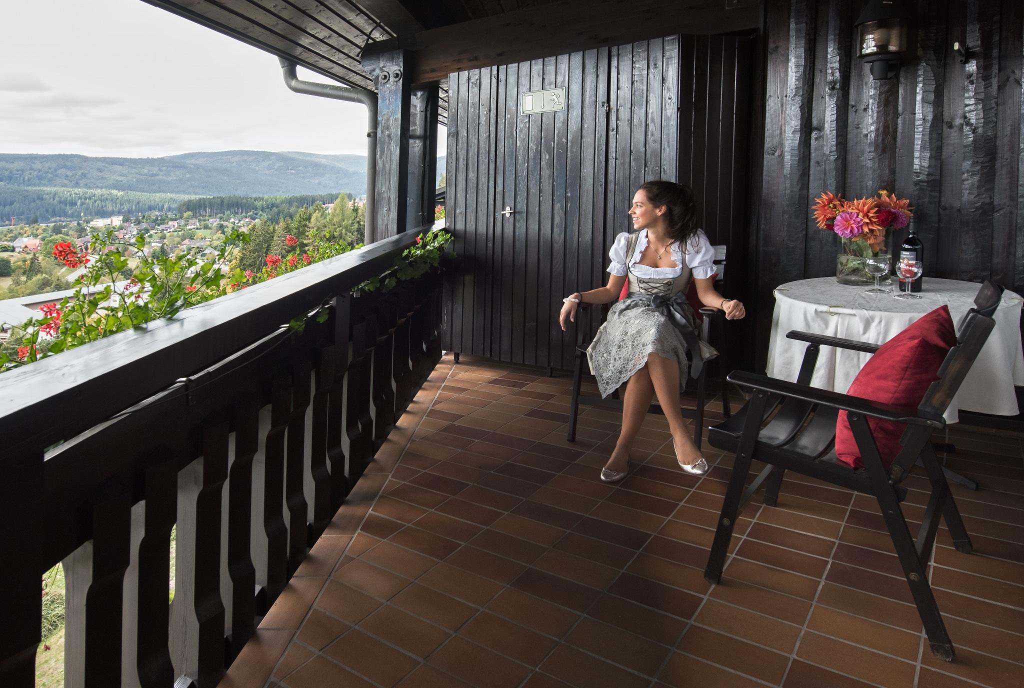 Frau im Dirndl auf Balkon im Vier Jahreszeiten am Schluchsee