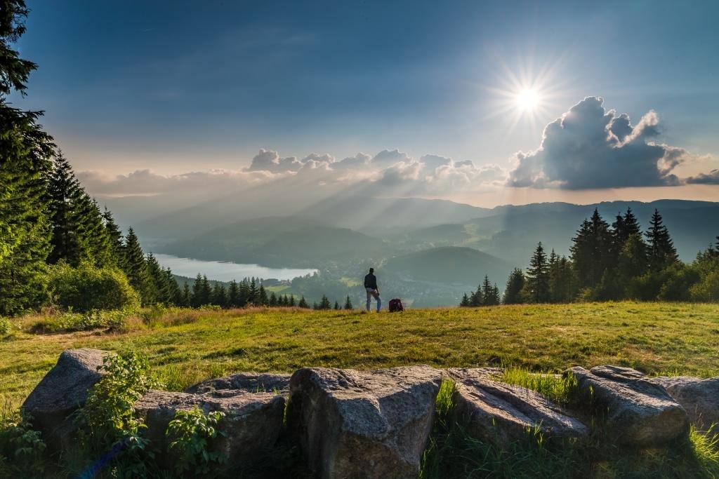 Wanderer auf einem Berg im Schwarzwald mit Blick auf einen See