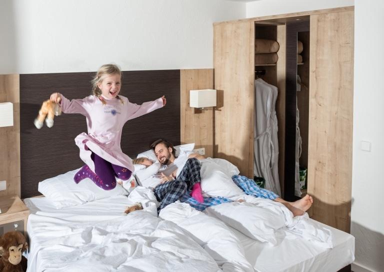 Kind springt auf dem Bett im Familienzimmer im Vier Jahreszeiten am Schluchsee