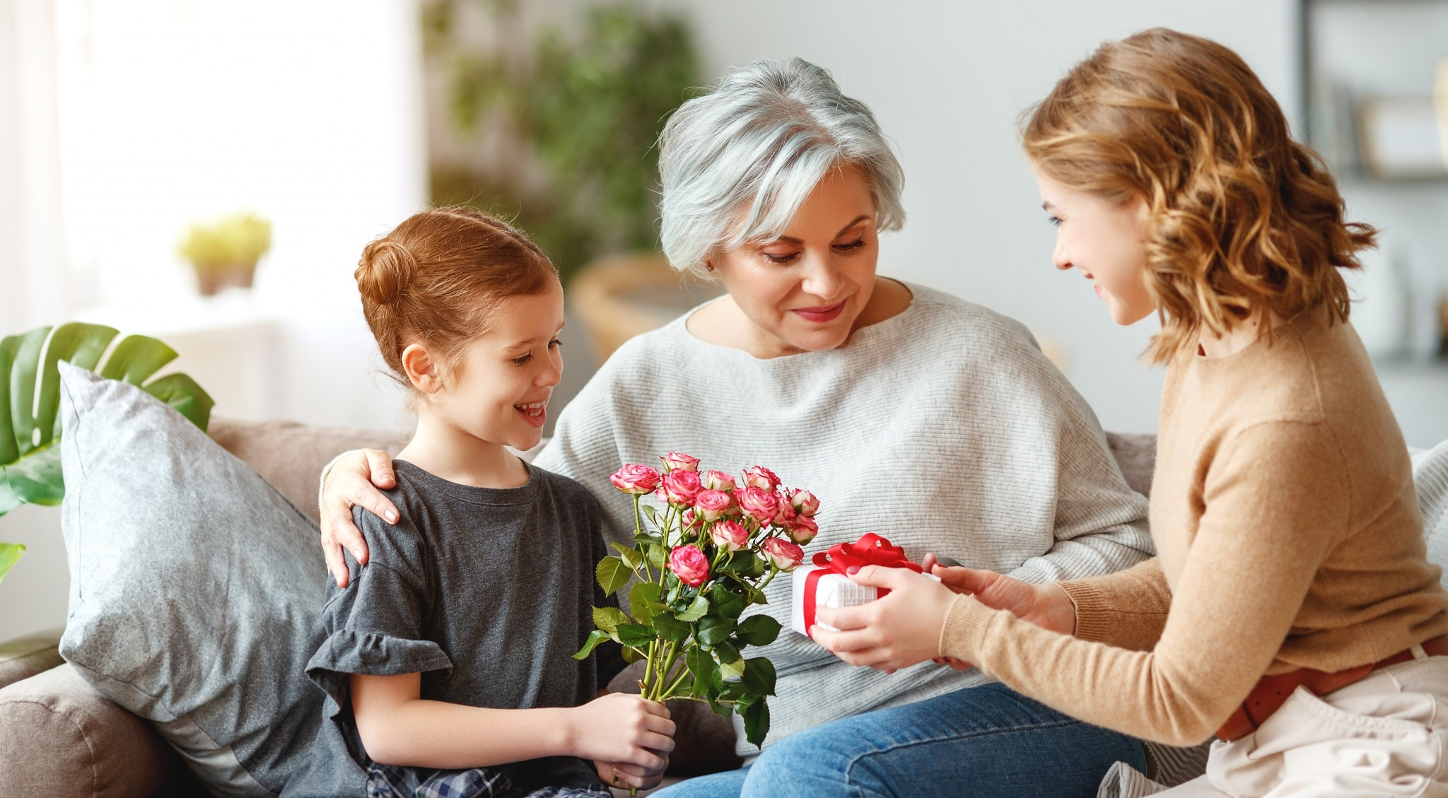 Mädchen mit Muter und Oma bei der Übergabe eines Geschenks an Oma