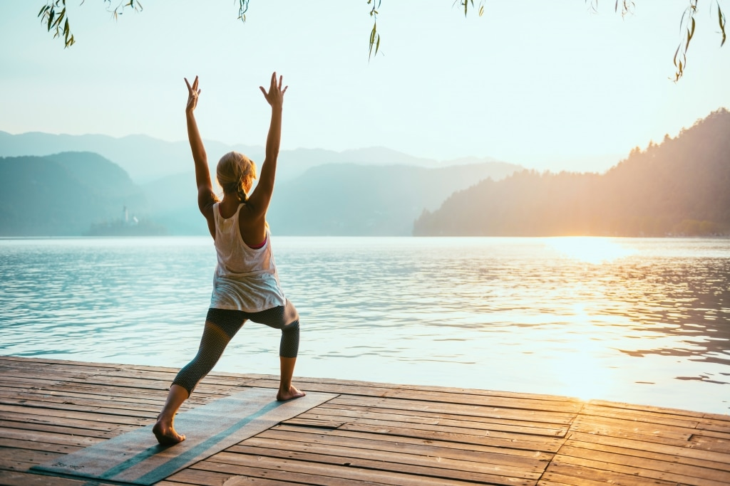 Frau in Yoga-Pose am See