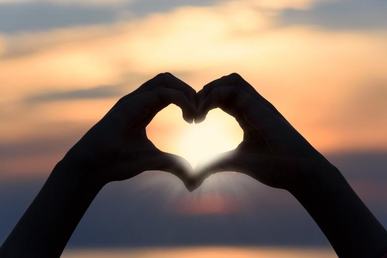 Hände die vor dem Sonnenuntergang zum Herz vereint sind