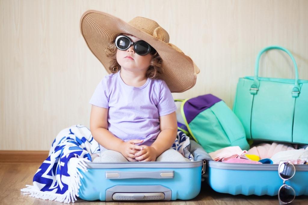 Kleines Mädchen mit Hut und Sonnenbrille im Koffer