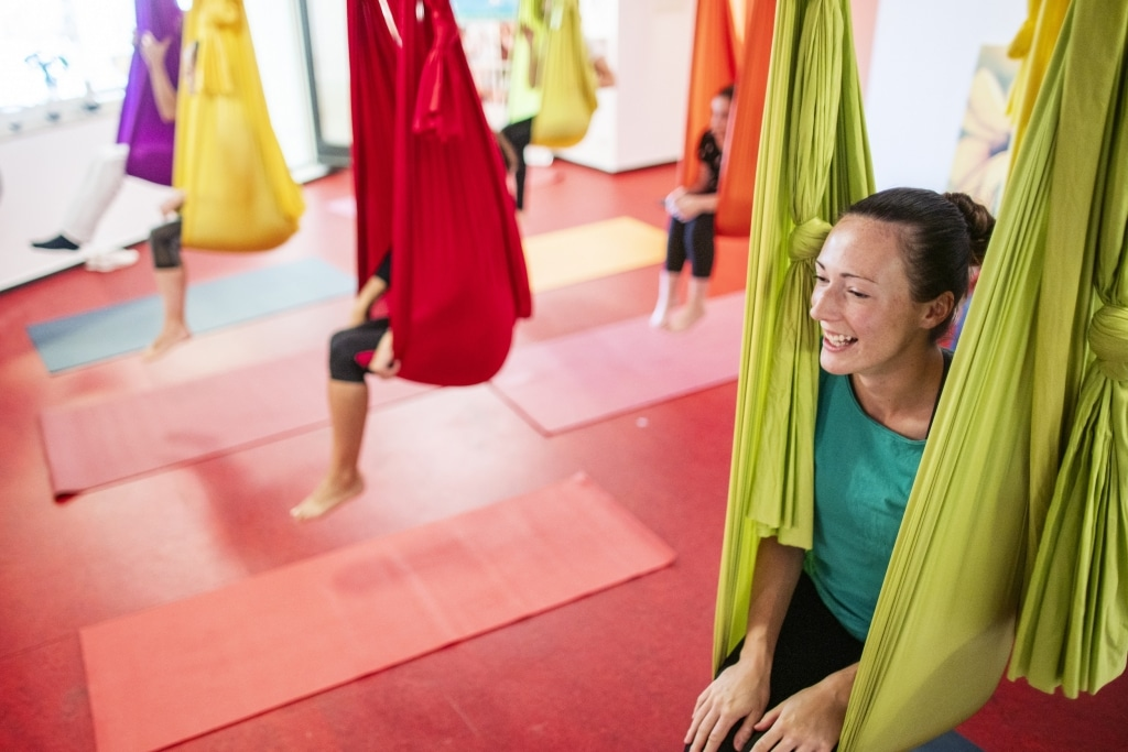 Gruppe sitzt beim Aerial Yoga in den Tüchern