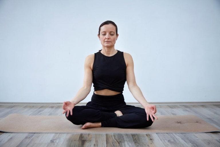 Frau in schwarzer Yoga-Kleidung beim Yoga im Hotel Vier Jahreszeiten