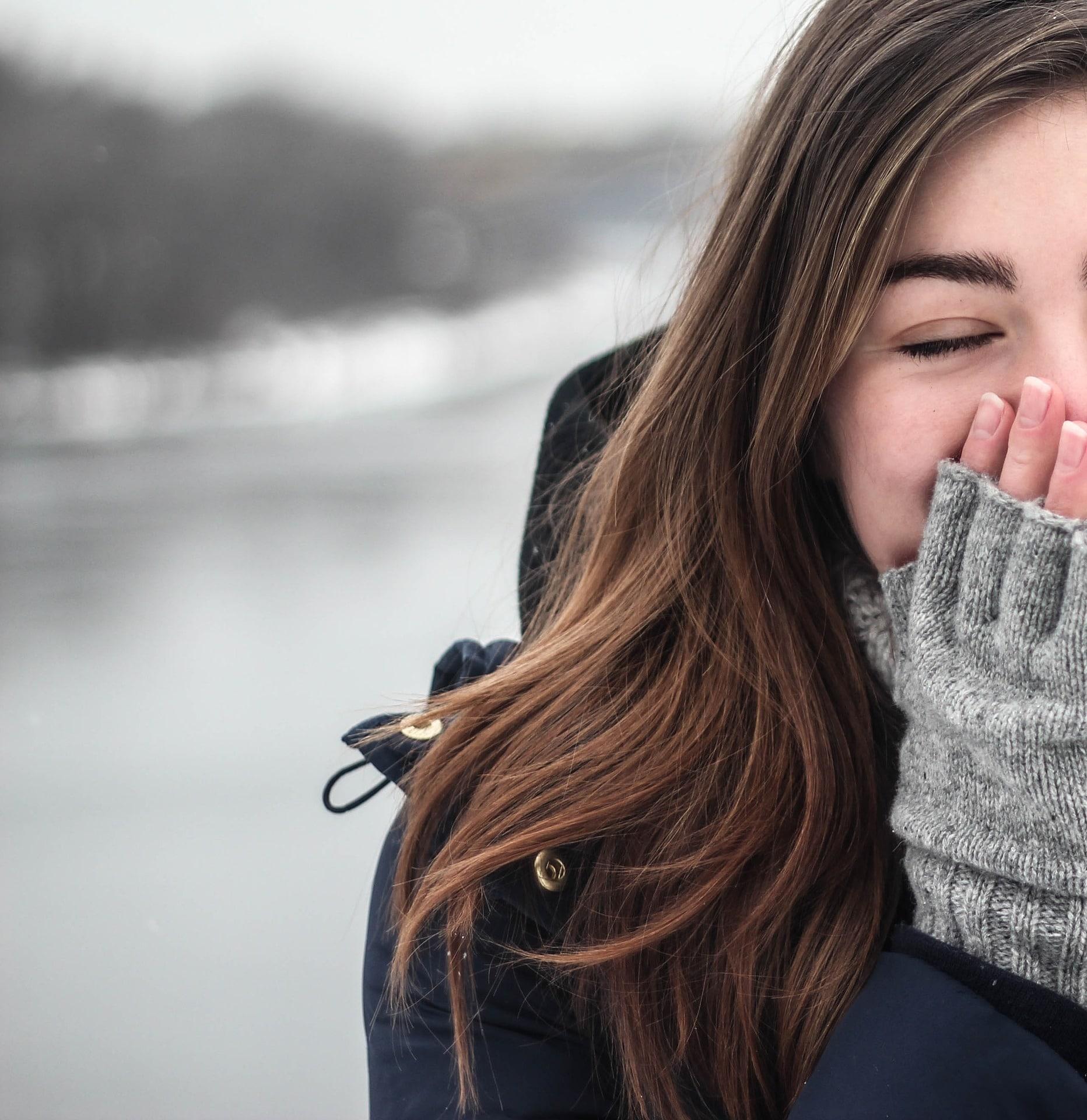 Frau im Winter pustet sich wärmend in die Hände