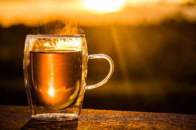Dampfende Tasse Tee im Sonnenuntergang