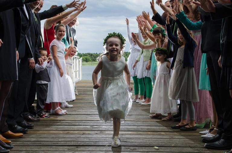 Hochzeitsgesellschaft am See - Blumenkind rennt durch die Mitte