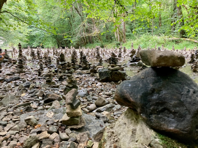 Viele kleine Steinstapel an einem Fluss