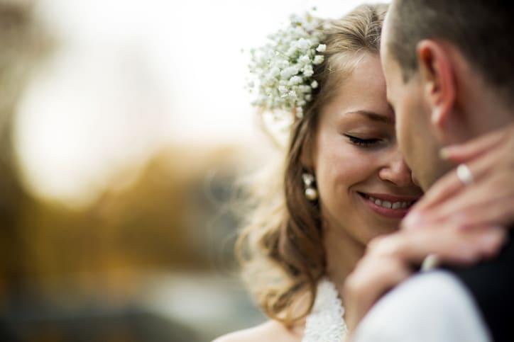 Braut mit Blumen im Haar umarmt den Bräutigam
