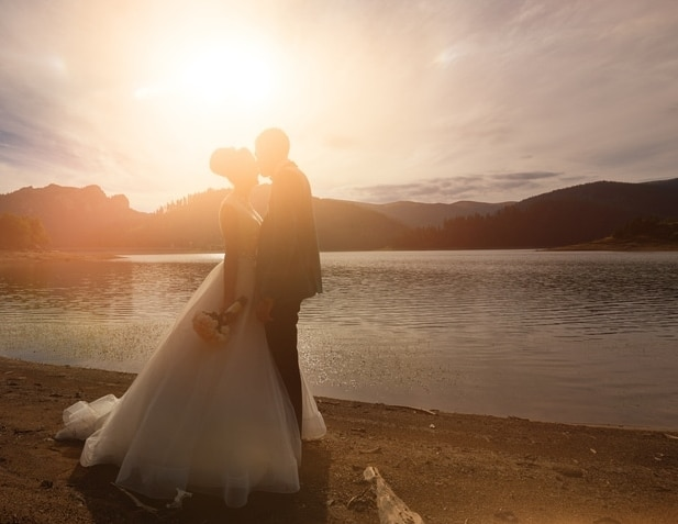 Brautpaar vor dem Sonnenuntergang am See