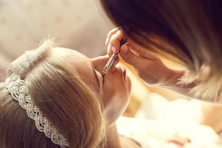 Braut bekommt ein Braut-Make-Up von einer Stylistin