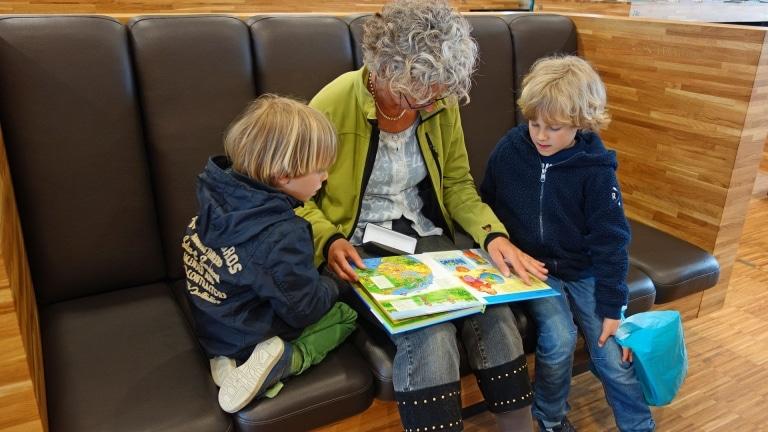 Oma und Kinder sitzen auf Couch und schauen gemeinsam ein Buch an