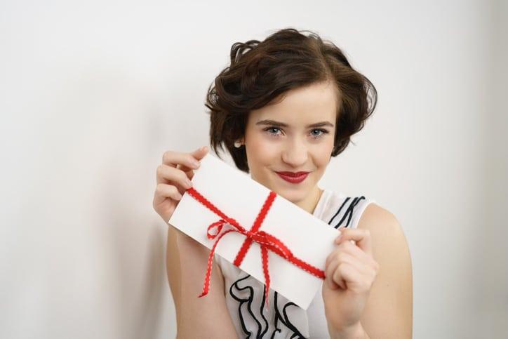 Frau hält Geschenkkarte in den Händen