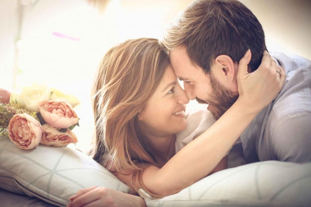Mann und Frau liegen romantisch auf Kissen