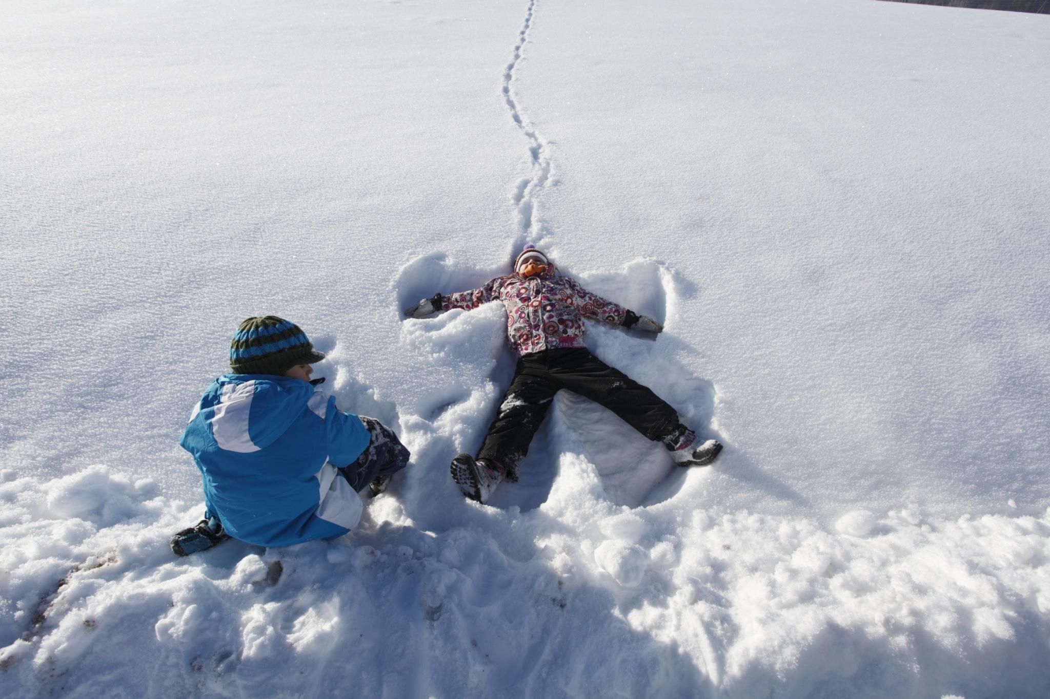 Kinder beim Schneeengel machen im Schnee