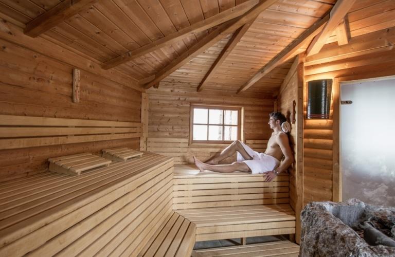 Mann sitzt in Blockhaus Sauna