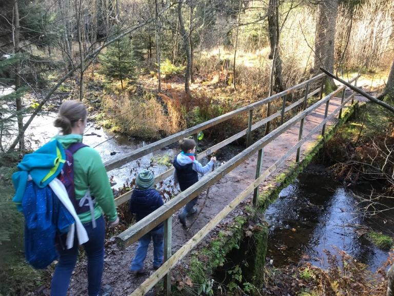 Frau und zwei Kinder gehen über kleine Brücke über einen Bach
